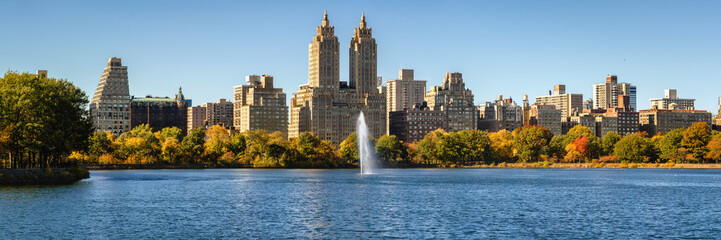Central Park and Manhattan Upper West Side with colorful Fall foliage and a panoramic view across Jacqueline Kennedy Onassis Reservoir with its fountain. Central Park West in autumn.  New York City