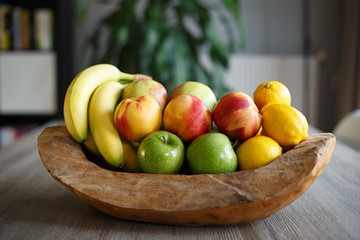 Wooden bowl filled with fresh fruit