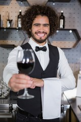 Bartender serving glass of red wine in bar counter