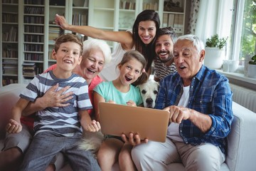 Portrait of happy multi generation using laptop