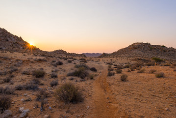 Colorful sunset over the Namib desert, Aus, Namibia, Africa. Sun star at the horizon, footpath crossing rocky desert.