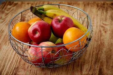 Metal fruit bowl on a wooden surface. Close. Bananas, oranges apples