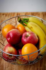 Metal fruit bowl on a wooden surface. Close. Bananas, oranges apples