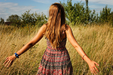 Young beautiful girl walking in the field and runs hand through the high dry grass at summertime