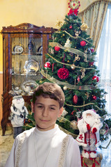 Boy with surplice near the Christmas tree