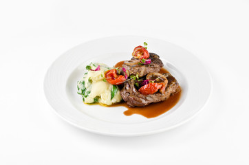 Braised beef on the bone with dried tomatoes and mashed potatoes with spinach and feta cheese on a plate on a white background