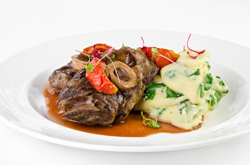 Braised beef on the bone with dried tomatoes and mashed potatoes with spinach and feta cheese on a plate on a white background, closeup