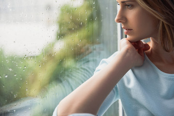 beautiful lonely woman sitting in front of window Wall mural