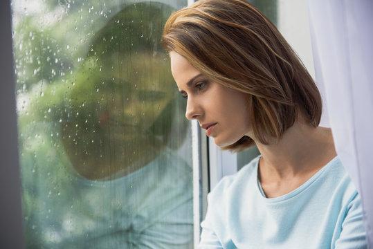 sad woman sitting indoors while raining