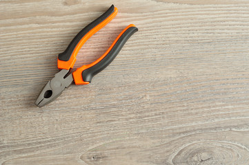 Pliers isolated on a wooden background