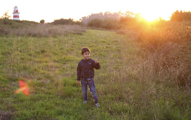 kid in a field at sunset
