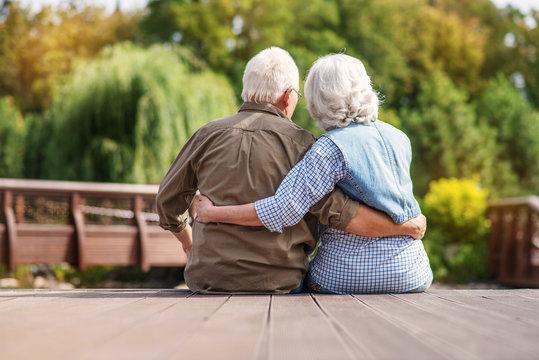Loving mature couple resting near lake