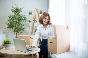 home, post, delivery and happiness concept - smiling young woman opening cardboard box at home.