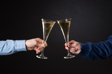 Two male hands holding champagne glasses isolated on black background