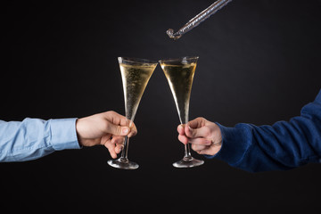 Two male hands holding champagne glasses and foil blowout isolated on black background