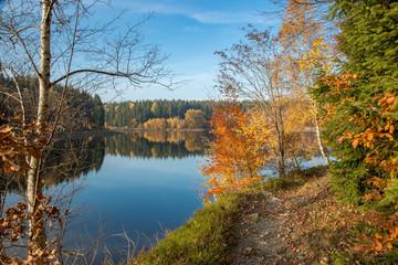 Spiegelungen der Herbstfärbung im blauen Wasser am Frankenteich im Südharz