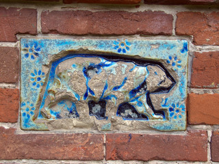 The old tile with a picture of a bear on a brick wall