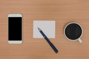 wooden desk with blank smart phone, coffee, paper note and pen