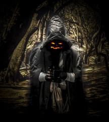 background image of halloween ghost with scary jack face, in the hood in dark forest