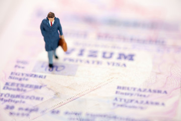 Toy businessman / View of miniature toy, businessman walking on passport. Travel concept.
