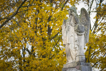 Crying angel statue at old cemetery in autumn. Mourns those who have died