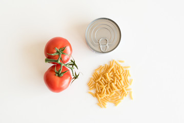 High angle view of tomatoes, tinned fish and macaroni on a white table
