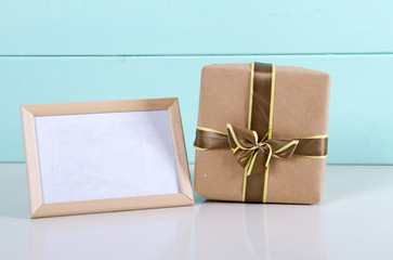 gift box in kraft paper and photo frame on wooden background.