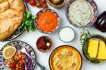 Mediterranean traditional meze: hummus, babaganoush, harissa, tzatziki on white background