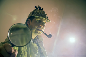 sherlock holmes in studio etective at work with magnifying glass and pipe