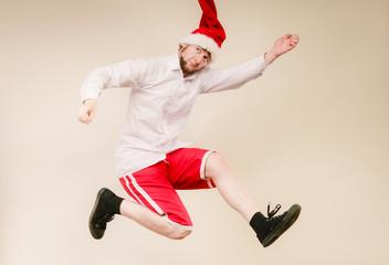 Active man in santa hat dancing and jumping.
