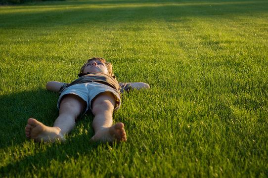 Pensive little boy lying on the grass barefoot