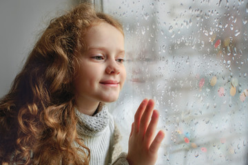 Happy child looking out the window with wet glass autumn bad wea