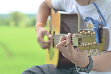 Young man playing guitar onoutdoor blur background, selective focus, copy space.