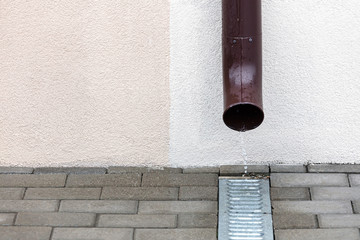 rain water flowing out from two metal gutters during rainy weather