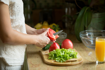 Hands cutting the tomatoes, salad, cucumber on the board, orange juice on the table