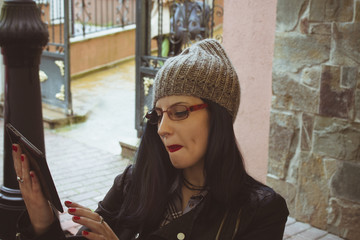 young woman with wool cap and tablet in town
