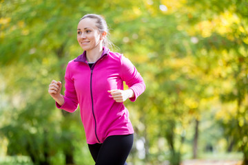 Portrait of an attractive smiling woman jogging in the fall time. Concept photo