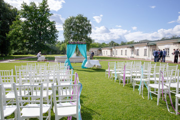 A look from behind on white chairs standing on the green lawn an