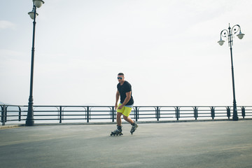 young man with inline skates ride in summer park seafront outdoor rollerskater