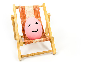 happy face on pink egg on beach chair abstract background for summer ,easter holiday concept.