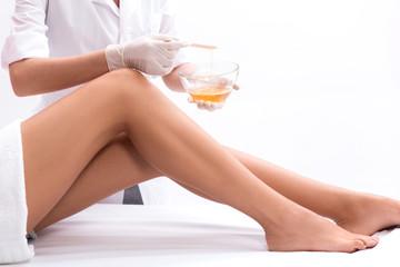 Skillful cosmetologist undergoing waxing procedure