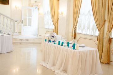 White table decorated with blue candles stand behind a big brigh
