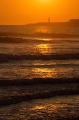 Couché de soleil orange, sur la mer, avec phare