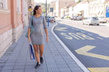 Cute young woman walking after shopping in store