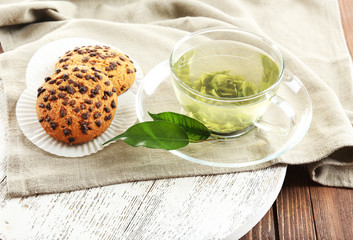 Glass cup of green tea and cookies on wooden table
