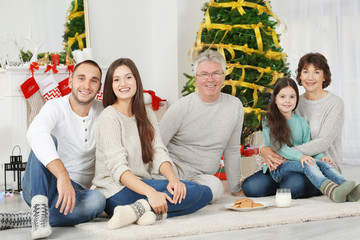 Happy family with cookies and milk in living room decorated for Christmas