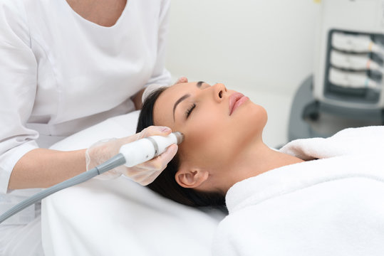 Young woman getting cavitation skin care treatment