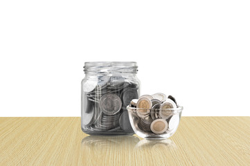 coins in a glass jar on Wood floor ,savings coins - Investment And Interest Concept saving money concept, growing money on piggy bank. isolated on white background
