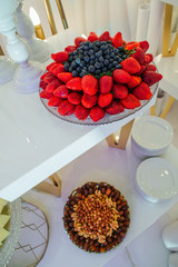 Plates with nuts and berries stand on the different layers on a