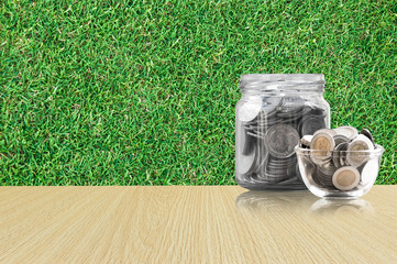 coins in a glass jar on Wood floor ,savings coins - Investment And Interest Concept saving money concept, growing money on piggy bank. isolated on grass background